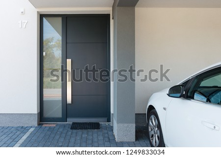 Modern house entrance with parking car next to it Royalty-Free Stock Photo #1249833034