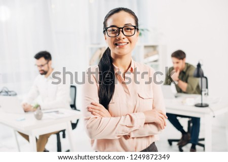 Smiling female manager standing with crossed arms in office  #1249872349