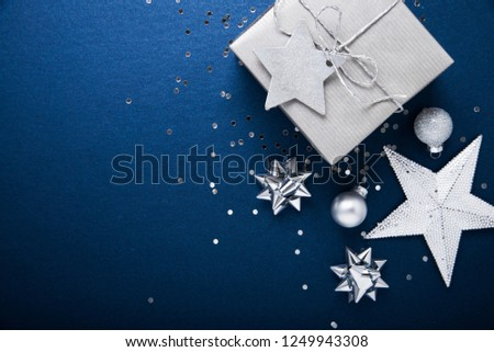 Merry Christmas and Happy Holidays greeting card, frame, banner. New Year. Noel. Silver Christmas gifts, ornaments on blue background top view. Winter holiday xmas theme. Flat lay. #1249943308