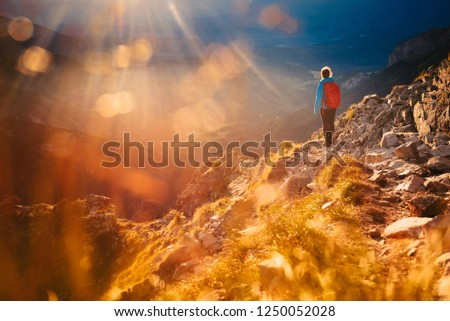 Alone woman standing in mountains in beautiful orange sunset light, Edit space. Adventure photo