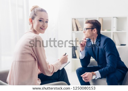 cheerful journalist taking notes during interview with businessman in office and looking at camera #1250080153