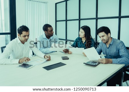 Business team analyzing financial report. Four multiracial professionals sitting at meeting table and discussing documents. Paperwork and teamwork concept #1250090713