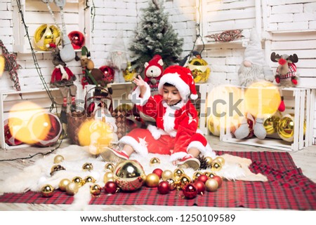 Baku, Azerbaijan - December 30, 2016 : A baby boy at the studio. A baby boy at. New Year Decoration. A baby boy in a red suit. New Year Decoration 2019. #1250109589