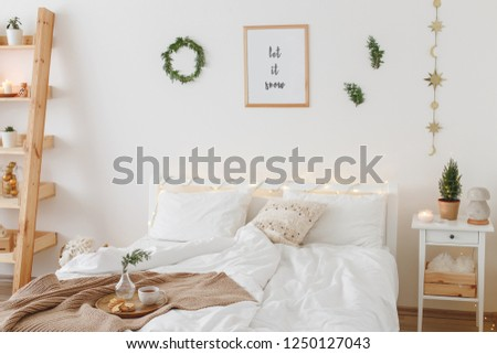 New year winter home interior decor. Christmas holiday decorations: little christmas tree, wreath, coniferous twigs, pine branches, led garland lights, blanket. White stylish cozy scandinavian bedroom #1250127043