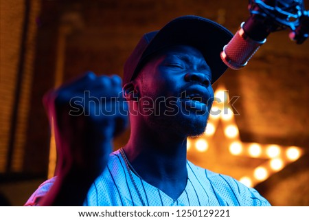 Man with beard and mustaches in baseball cap and t-shirt sing in microphone. Pink and blue neon light, star on background #1250129221