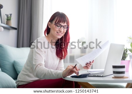 Happy woman at home using laptop and checking bills and invoice document #1250143741