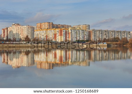 Microdistrict in the West of Krasnodar and its reflection in the Kuban River at sunset. Two worlds in one place. #1250168689