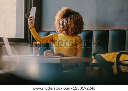 Smiling afro american woman taking a selfie on mobile phone sitting at a restaurant with snacks and laptop on table. Female tourist dining at a restaurant while working on laptop and taking selfie.