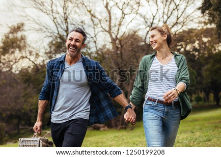 Happy couple walking in the park holding hand and carrying picnic basket. Loving couple going on a picnic at the park. #1250199208