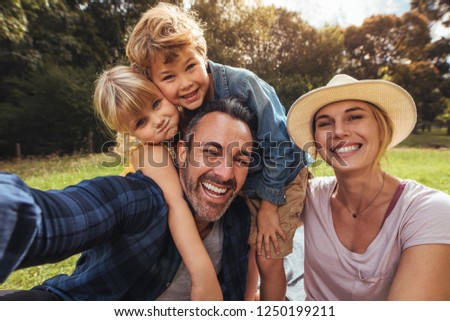 Cheerful family making selfie. Parents having fun with their kids outdoors at park. Cute family having picnic. #1250199211