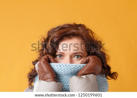 Portrait of a young woman on a yellow background. The beautiful brunette wears knitted snood, leather gloves. The concept of winter. #1250199601
