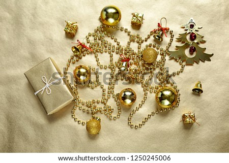 Christmas flat lay of yellow toys on golden paper background, holiday concept, top view #1250245006