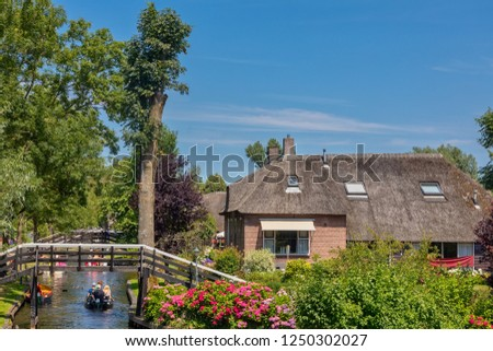 Giethoorn, Netherlands - July 4, 2018: view of famous village Giethoorn with canals in the Netherlands. Giethoorn is also called 'Venice of The Netherlands'  #1250302027