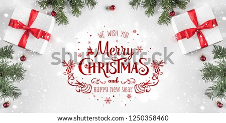Merry Christmas Typographical on white background with gift boxes, fir branches, red decoration. Xmas and New Year card, bokeh, light. Flat lay, top view #1250358460