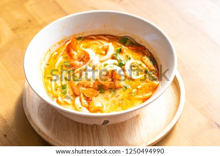 Thai Tom Yum Kung  spicy food in the bowl   on wooden tray and on wooden backgrounds.  #1250494990