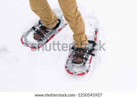 close-up, walking in the snow in special devices, snowshoes, for better maneuverability #1250545927
