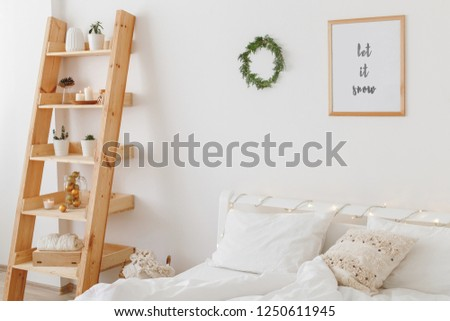 New year winter home interior decor. Simple Christmas holiday decorations: wreath of pine branches, led garland lights, frame with text LET IT SNOW. White stylish cozy scandinavian bedroom. #1250611945