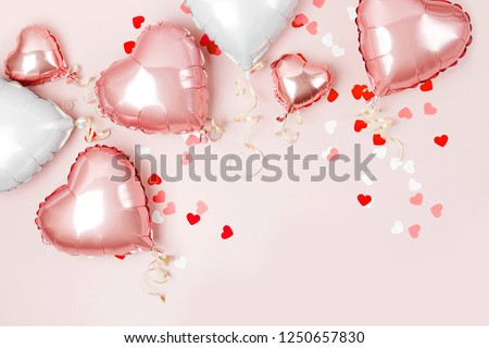 Air Balloons of heart shaped foil  on pastel pink background. Love concept. Holiday celebration. Valentine's Day or wedding/bachelorette party decoration. Metallic balloon #1250657830