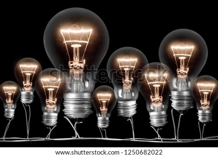 Photo of shining light bulbs; concept of idea and innovation; isolated on black background #1250682022