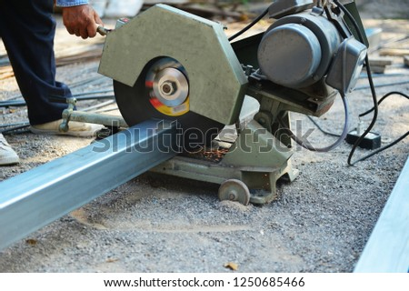 Worker is using cutting maching cutting steel pipe. #1250685466
