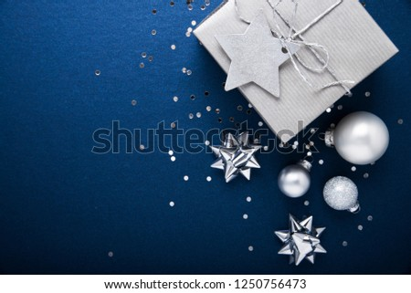 Merry Christmas background and Happy Holidays greeting card, frame. New Year. Noel. Silver Christmas gifts, decorations, ornaments on blue background top view. Winter holiday xmas theme. Flat lay. #1250756473