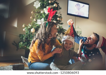 Happiness is in their home. Family at home enjoys pre-Christmas holidays. #1250806093