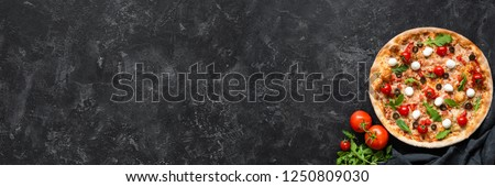 Pizza with tomatoes, mozzarella cheese, arugula and sauce on black stone background. Web banner, menu for restaurant or cafe, recipe concept. Copy space for text #1250809030