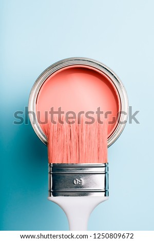 Brush with white handle on open can of Living Coral paint on blue pastel background. Color of the year 2019. Main trend concept. #1250809672