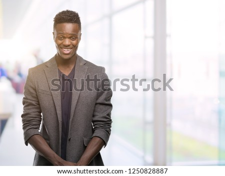 Young african american man wearing a jacket with a happy face standing and smiling with a confident smile showing teeth #1250828887