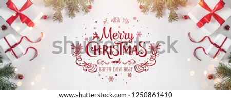 Merry Christmas Typographical on white background with gift boxes, fir branches, red decoration. Xmas and New Year card, bokeh, light. Flat lay, top view #1250861410