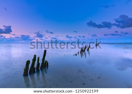 A beautiful calm and tranquil sunset over the Wadden sea with a colourful sky and clouds - Unesco world heritage site Wadden sea, Friesland, The Netherlands #1250922199