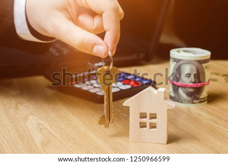 Realtor holds house keys. Real estate agent. Buying and selling a house, apartment. Home. Affordable housing. Investment in construction. Planning a new project. Property valuation. Selective focus #1250966599