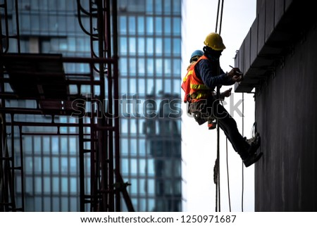 Construction worker wearing safety harness and safety line working at high place #1250971687