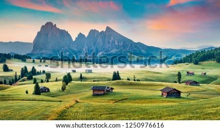 Breathtaking morning scene of Compaccio village, Seiser Alm or Alpe di Siusi location, Bolzano province, South Tyrol, Italy, Europe. Fantastic summer sunrise of Dolomiti Alps.  #1250976616