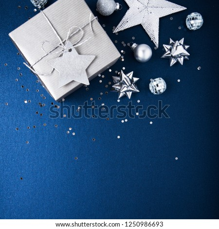 Merry Christmas and Happy Holidays greeting card, frame, banner. New Year. Noel. Silver Christmas gifts, ornaments on blue background top view. Winter holiday xmas theme. Flat lay. #1250986693