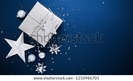 Merry Christmas and Happy Holidays greeting card, frame, banner. New Year. Noel. Silver Christmas gifts, ornaments on blue background top view. Winter holiday xmas theme. Flat lay. #1250986705