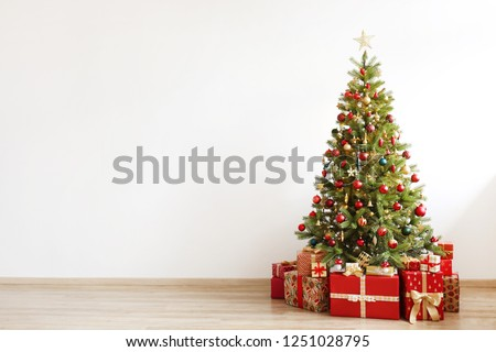 Big beautiful christmas tree decorated with beautiful shiny baubles and many different presents on wooden floor. White wall background with a lot of copy space for text. Close up. #1251028795