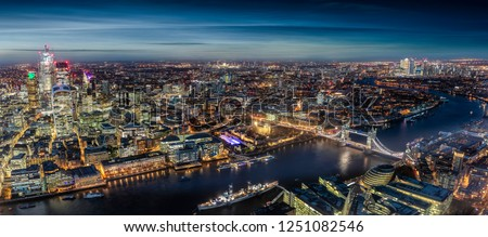 Wide panorama of London, UK, by night: from the City along the Thames river to Tower Bridge and Canary Wharf #1251082546