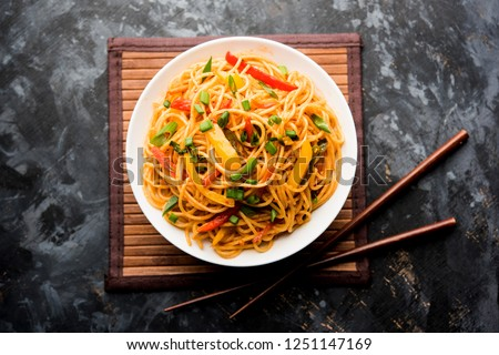 Schezwan Noodles or vegetable Hakka Noodles or chow mein is a popular Indo-Chinese recipes, served in a bowl or plate with wooden chopsticks. selective focus #1251147169