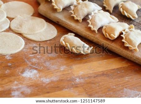 Raw meat pelmeni, ravioli, dumplings on a wooden board #1251147589