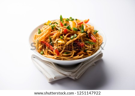 Schezwan Noodles or vegetable Hakka Noodles or chow mein is a popular Indo-Chinese recipes, served in a bowl or plate with wooden chopsticks. selective focus #1251147922
