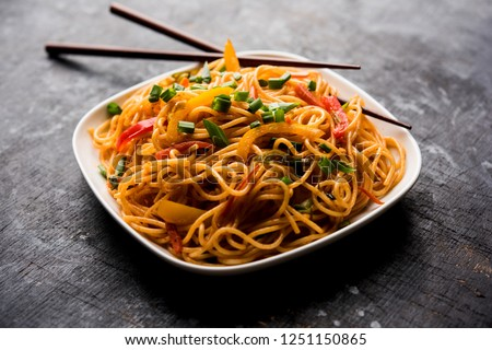 Schezwan Noodles or vegetable Hakka Noodles or chow mein is a popular Indo-Chinese recipes, served in a bowl or plate with wooden chopsticks. selective focus #1251150865