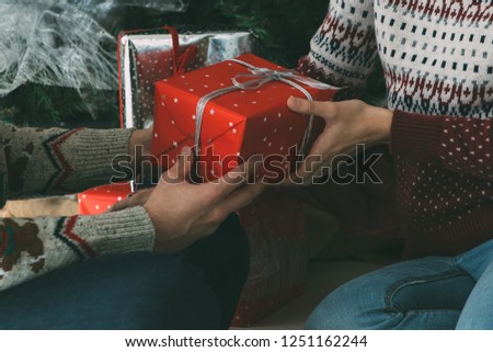 Cropped view of a young woman is receiving a Christmas gift from her beloved man under the fir tree and wearing Christmas sweaters #1251162244