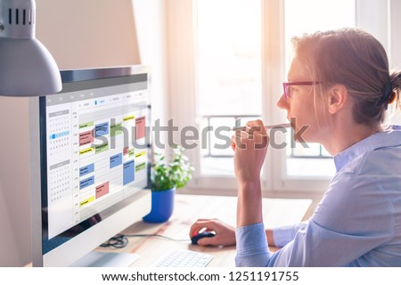 Person using calendar on computer to improve time management, plan appointments, events, tasks and meetings efficiently, improve productivity, organize week day and work hours, business woman, office Royalty-Free Stock Photo #1251191755