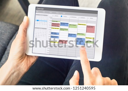 Calendar app on tablet computer with planning of the week with appointments, events, tasks, and meeting. Hands holding device, time management concept, organization of working hours planner, schedule #1251240595