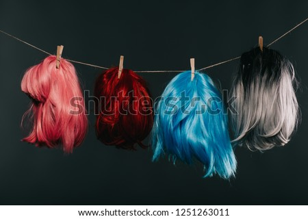 four colorful wigs hanging on rope isolated on black Royalty-Free Stock Photo #1251263011