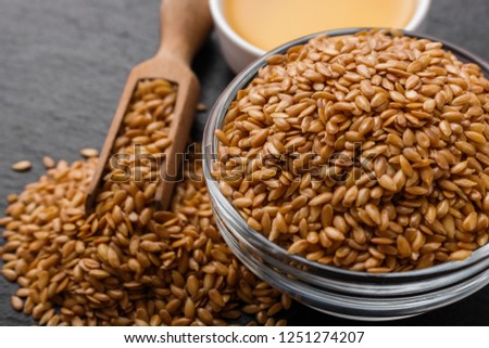 seeds of golden flax on a dark stone background #1251274207