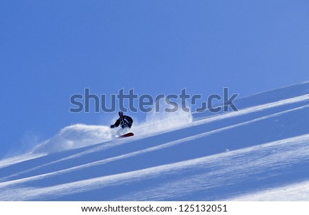 Active man snowboarding in fresh snow in Alaska's Chugach Mountains in winter #125132051