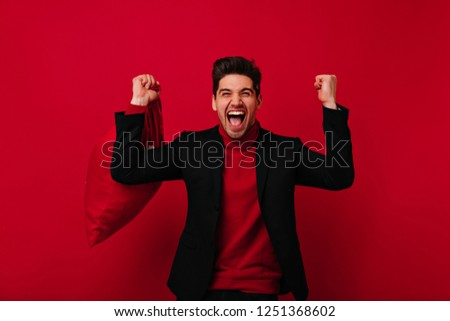 Joyful man with trendy haircut expressing happiness on red background. Refined caucasian guy posing in black jacket. #1251368602