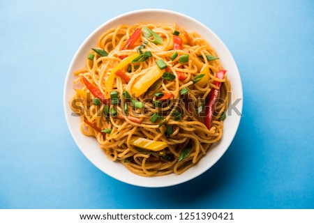 Schezwan Noodles or vegetable Hakka Noodles or chow mein is a popular Indo-Chinese recipes, served in a bowl or plate with wooden chopsticks. selective focus #1251390421